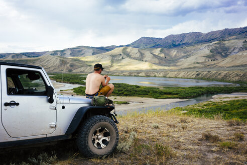Shirtless man holding fishing rod while sitting on SUV in front of mountains at Grand Teton National Park - TGBF01800