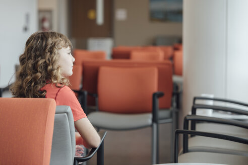 Thoughtful girl sitting on chair waiting for her checkup in hospital - TGBF01830