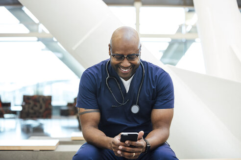 Smiling mature male surgeon using mobile phone in hospital - TGBF01839