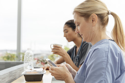 Side view of mature surgeon using mobile phone during break at hospital - TGBF01842