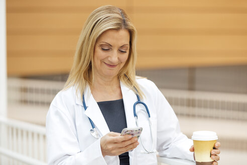 Smiling mature female doctor using mobile phone while holding coffee cup in hospital - TGBF01857