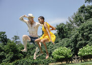 Low angle view of couple jumping into swimming pool against sky - CAVF57643