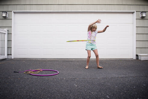 Girl playing with plastic hoop while standing on street against garage - CAVF57649