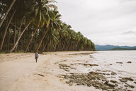 Rear view of woman walking at beach by coconut palm trees against sky - CAVF57652