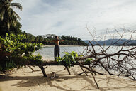 Rear view of carefree young woman with arms outstretched standing on fallen tree by dog at beach - CAVF57661