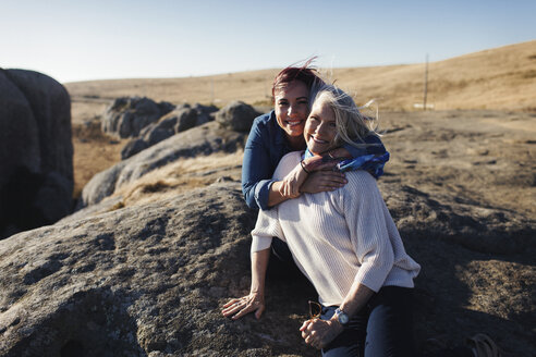 Portrait of cheerful mother and daughter on rocks against clear sky - CAVF57733