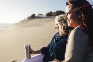 Mother and daughter looking at view while sitting on beach during sunny day - CAVF57739