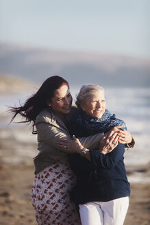 Cheerful daughter embracing mother at beach during sunny day - CAVF57742