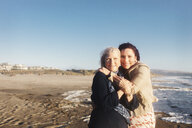 Portrait of happy mother and daughter at beach against clear sky during sunny day - CAVF57745