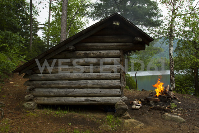 Campfire by log cabin in forest - CAVF57751
