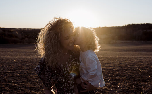 Loving daughter kissing cheerful mother while being carried by her on field during sunset - CAVF57778