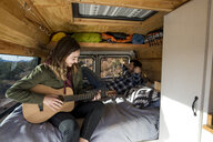 Woman playing guitar while sitting with friend in motor home - CAVF57784