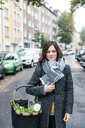 Mature woman standing in the street, carrying shopping basket with fresh vegetables - MOEF01704