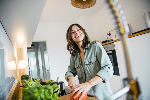 Laughing woman slicing pumpkin in her kitchen - MOEF01713