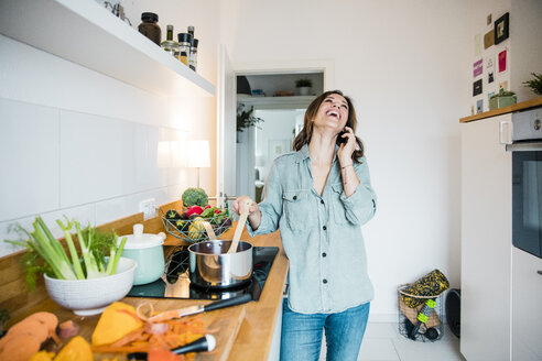 Laughing woman talking on the phone, while preparing pumpkin soup - MOEF01716