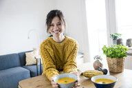 Woman presenting her pumpkin soup - MOEF01743