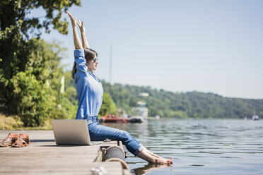 Woman with laptop sitting on a jetty at a lake, stretching - MOEF01770