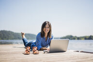 Mature woman working at a lake, using laptop on a jetty - MOEF01773