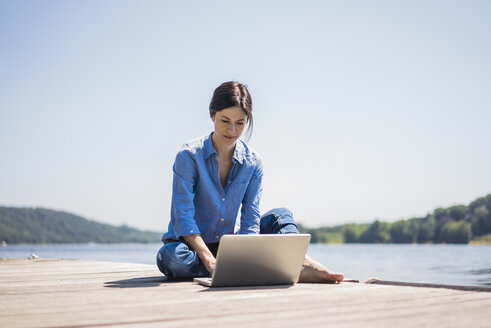Mature woman working at a lake, using laptop on a jetty - MOEF01776