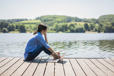 Mature woman sitting on a jetty at a lake, taking a break - MOEF01779