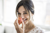 Laughing woman smelling an apricot - MOEF01791