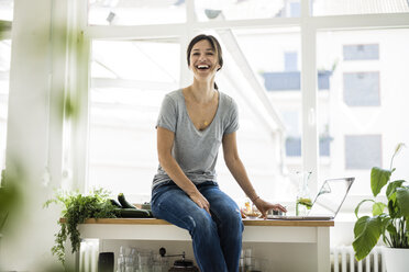 Woman sitting on kitchen table, searching for healthy recipes, using laptop - MOEF01806