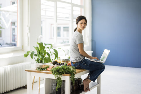 Woman sitting on kitchen table, searching for healthy recipes, using laptop - MOEF01809