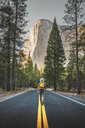 USA, California, Yosemite National Park, man walking on road with El Capitan in background - KKAF03032