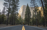 USA, California, Yosemite National Park, man with raised arms on road with El Capitan in background - KKAF03035