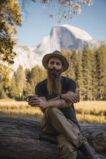 USA, California, portrait of bearded man sitting on a log in Yosemite National Park - KKAF03059