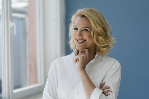Portrait of smiling blond woman wearing white shirt at the window - KNSF05393