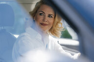 Smiling businesswoman in car looking sideways - KNSF05399