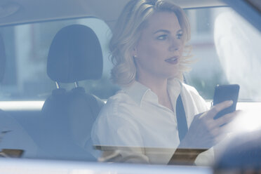 Businesswoman using cell phone while driving car - KNSF05402