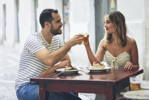 Smiling couple clinking beer in a restaurant on the street - JSMF00597