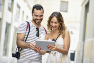 Spain, Andalusia, Malaga, happy tourist couple in the city looking at tablet - JSMF00600