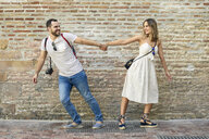 Happy couple holding hands walking in opposite directions at brick wall - JSMF00603