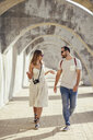 Spain, Andalusia, Malaga, tourist couple walking under an archway in the city - JSMF00618