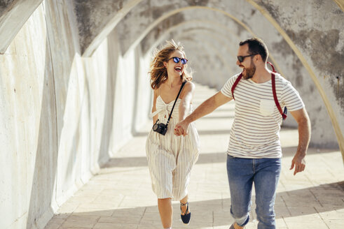 Spain, Andalusia, Malaga, carefree tourist couple running under an archway in the city - JSMF00621