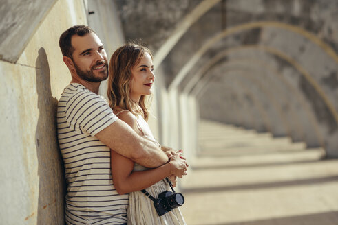 Spain, Andalusia, Malaga, affectionate tourist couple hugging under an archway in the city - JSMF00627