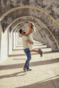 Spain, Andalusia, Malaga, happy man lifting up girlfriend under an archway in the city - JSMF00630