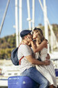 Spain, Andalusia, Malaga, affectionate tourist couple kissing at the harbor - JSMF00633