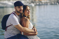 Spain, Andalusia, Malaga, affectionate tourist couple hugging at the harbor - JSMF00636