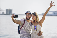 Spain, Andalusia, Malaga, happy tourist couple taking selfie with smartphone at the coast - JSMF00639