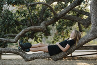 Side view of carefree girl lying on branch at farm - CAVF57798