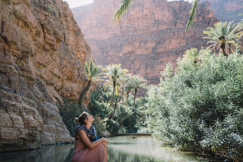 Woman looking up while sitting by lake against mountains - CAVF57807