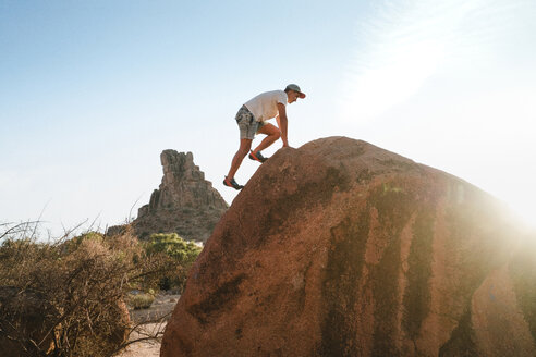 Low angle view of man climbing on rock against clear sky at desert - CAVF57810