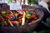 High angle view of chili peppers for sale in wicker basket at market stall - CAVF57822