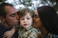 Portrait of cute son with parents kissing on field - CAVF57846