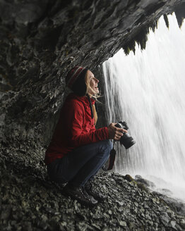 Cheerful female hiker looking at waterfall while holding camera - CAVF57927