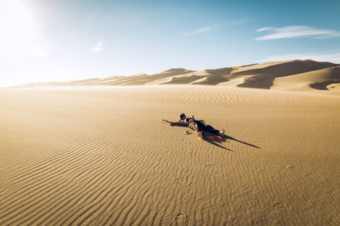 Carefree woman lying on sand at Great Sand Dunes National Park during sunny day - CAVF57936